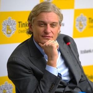 Олег Тиньков на фоне логотипа ТКС